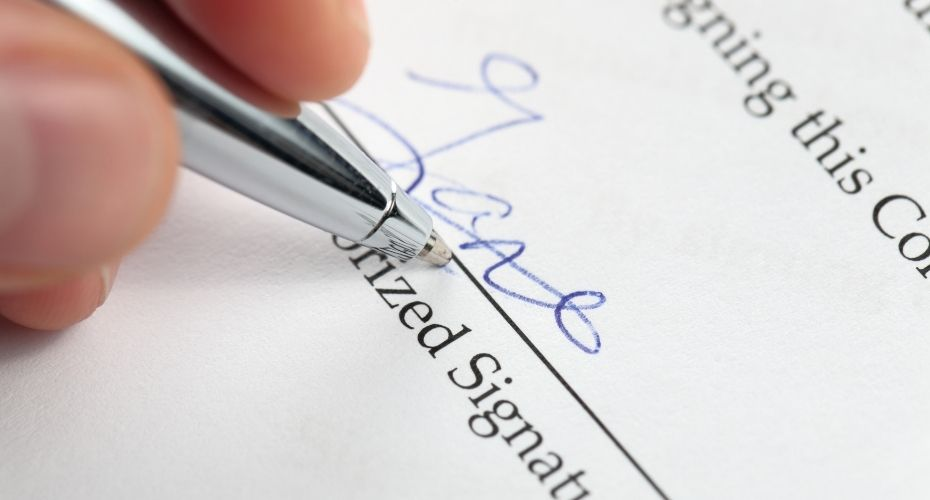 A silver pen signs the signature section of a Will.