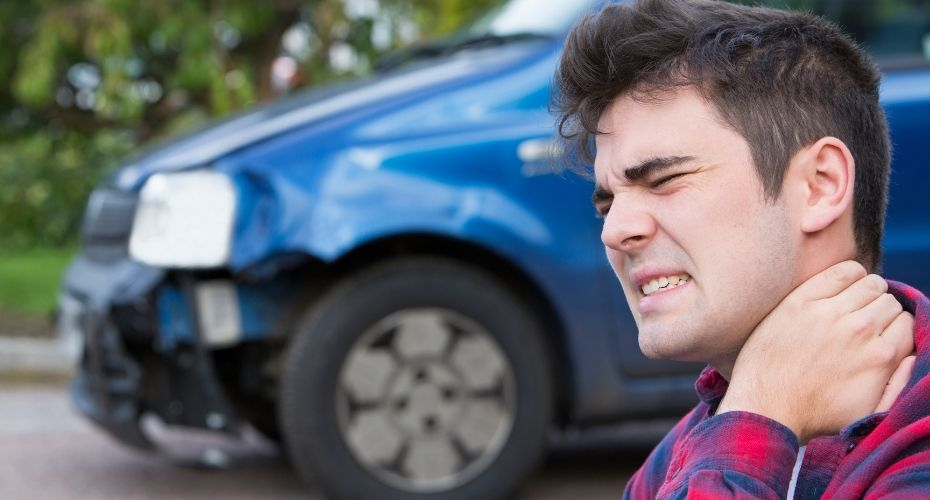 The driver of a vehicle has a pained face while standing near their smashed car and holding their neck.