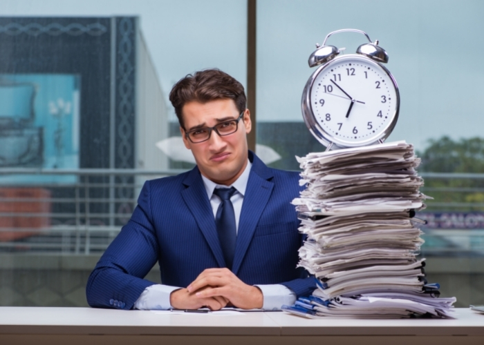 A person looking unhappy sitting next to a stack of forms with a ticking clock balancing on top.