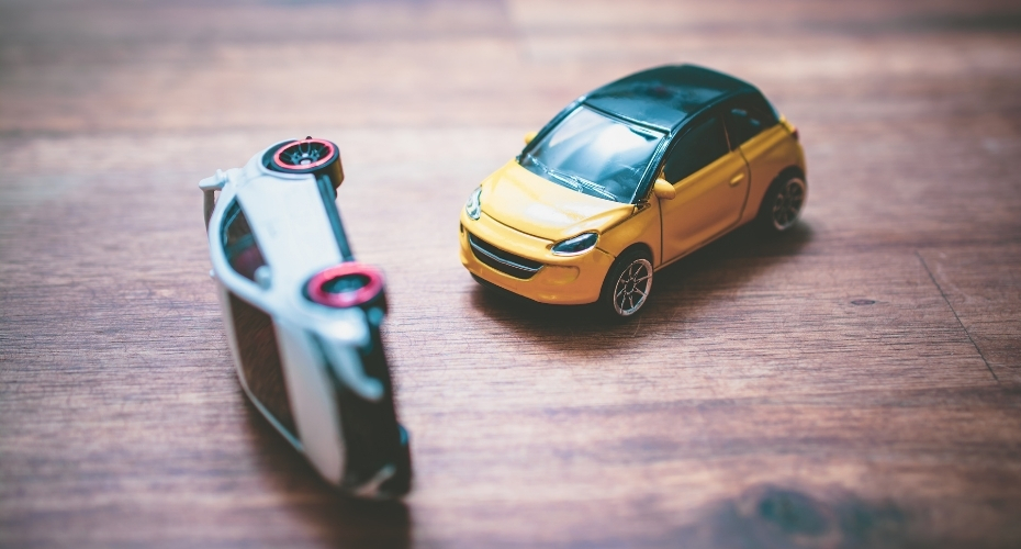 A toy car is flipped onto it's side after being crashed into by another toy car.
