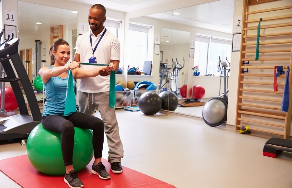 A woman does physiotherapy exercises while the physiotherapist looks on.