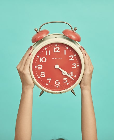 Two hands holding a red and beige alarm clock up high.