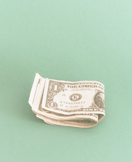 A stash of dollar bills, isolated on a green background.