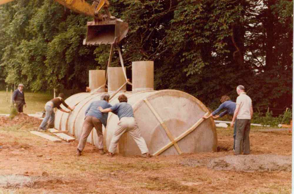 A group of men, with a crane installing the septic tank.