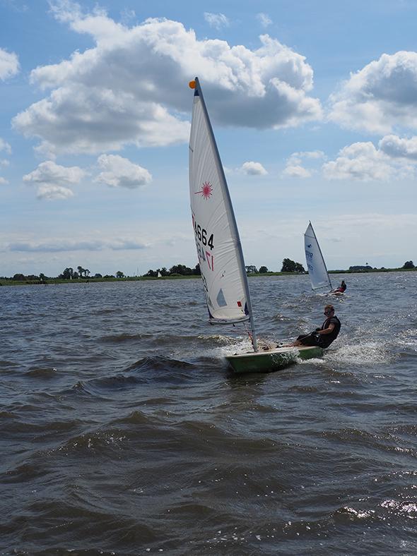 Ik zeil in een eenmansboot (een Laser) richting de camera, op de achtergrond zie je een zelfde boot die achter mij aan zeilt. We varen op het Heegermeer, het is een zonnige, mooie dag.