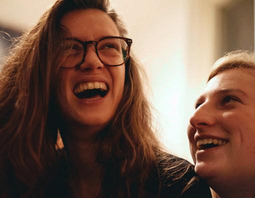 Een ingezoomde foto van mijn vriendin en ik. Ik zit bij haar op schoot en lach om iets of iemand buiten beeld, zij moet ook lachen en kijkt naar mij.