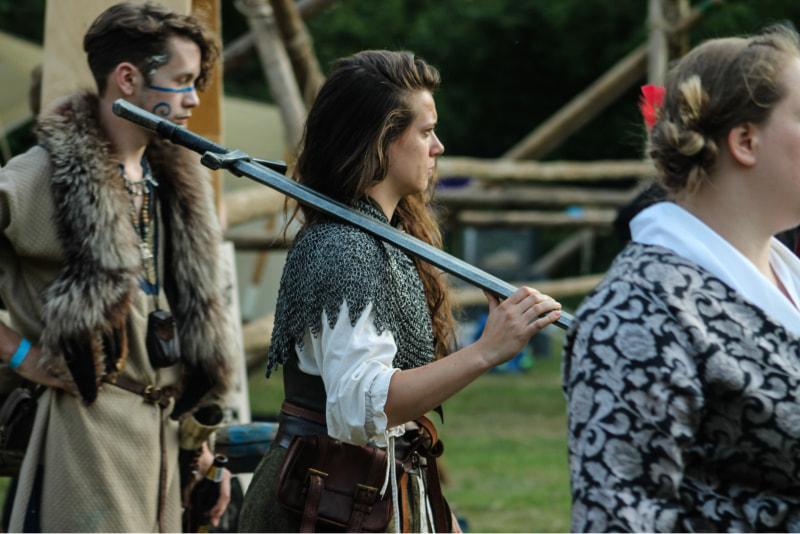 Foto van mij op een larp evenement. Ik heb een middeleeuws, fantasy kostuum aan en loop met een zwaard op mijn schouder.