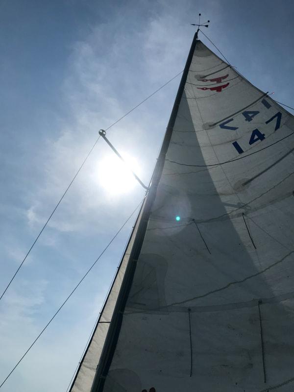 De top van het zeil van een zeilboot, precies zichtbaar in de zon.