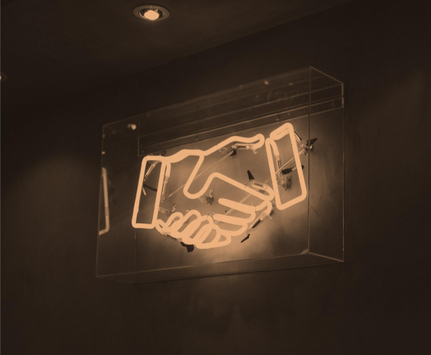 yellow neon sign of a handshake