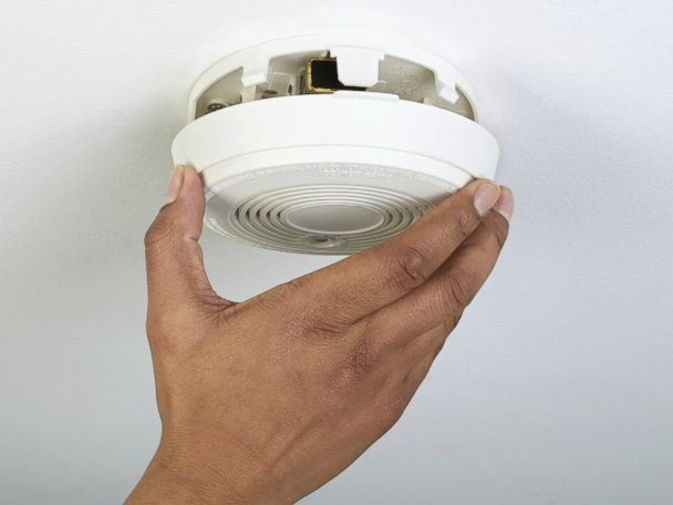 person removing smoke alarm from roof