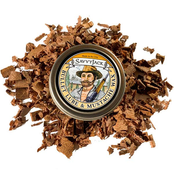 Strong hold SavvyJack mustache wax 1 oz tin. Front of mustache wax tin on wood chips.