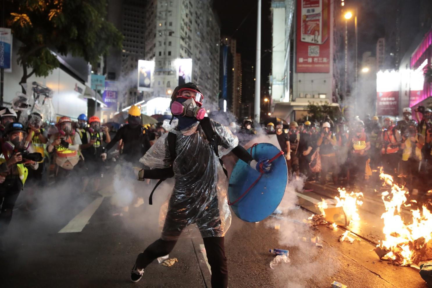 Image of Hong Kong Protester throwing rocks at riot police