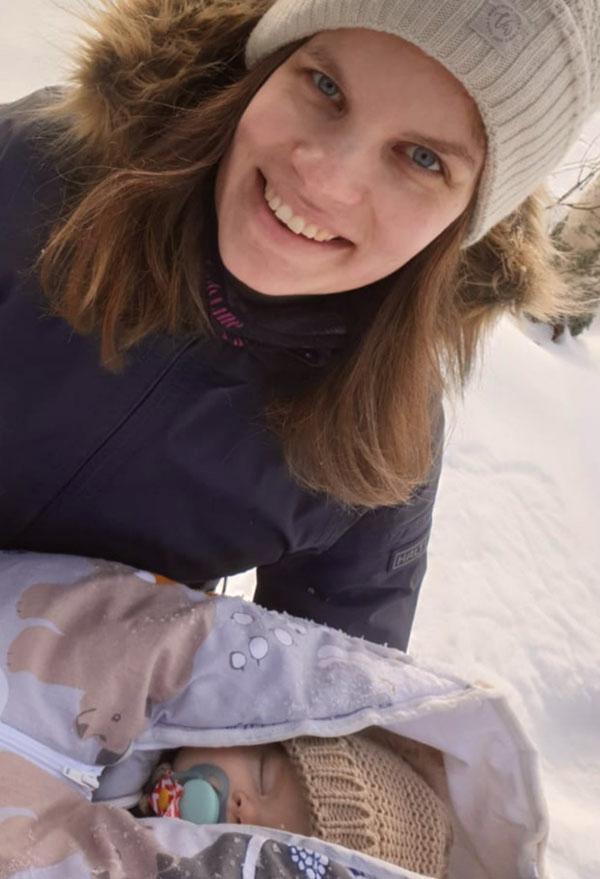 Nainen hymyilee vauva sylissä