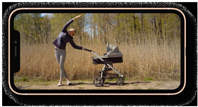 Puhelin jossa kuva hymyilevästä ohjaaja Johanna Salosesta joka näyttää miten tehdään Pilatesta lastenvaunujen kanssa