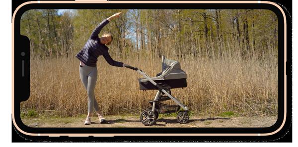 Iphone jossa Mama Moves kurssin ohjaaja Johanna Salonen  tekee jooga/pilates liikettä lastenvaunuista tukea pitäen