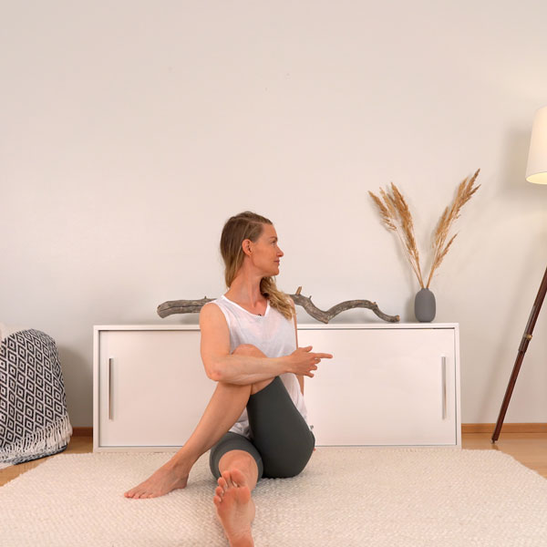 Liikunnanohjaaja (amk) Johanna Salonen näyttää jooga Pilates liikettä olohuoneen matolla, jonka avulla pääset kuntoon raskauden ja synnytyksen jälkeen