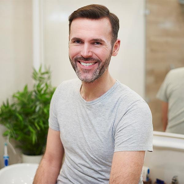 Man smiling in bathroom
