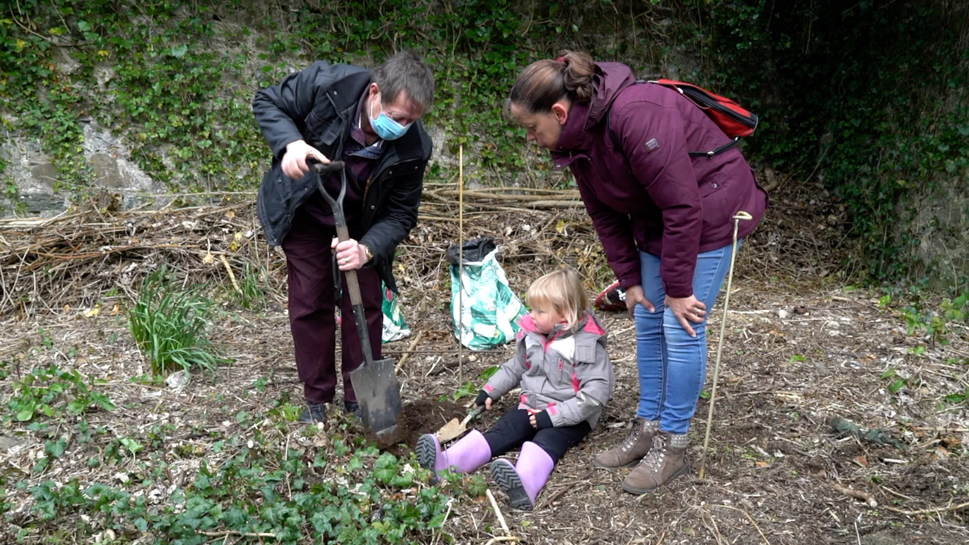 Photo of two adults and a small child planting a tree