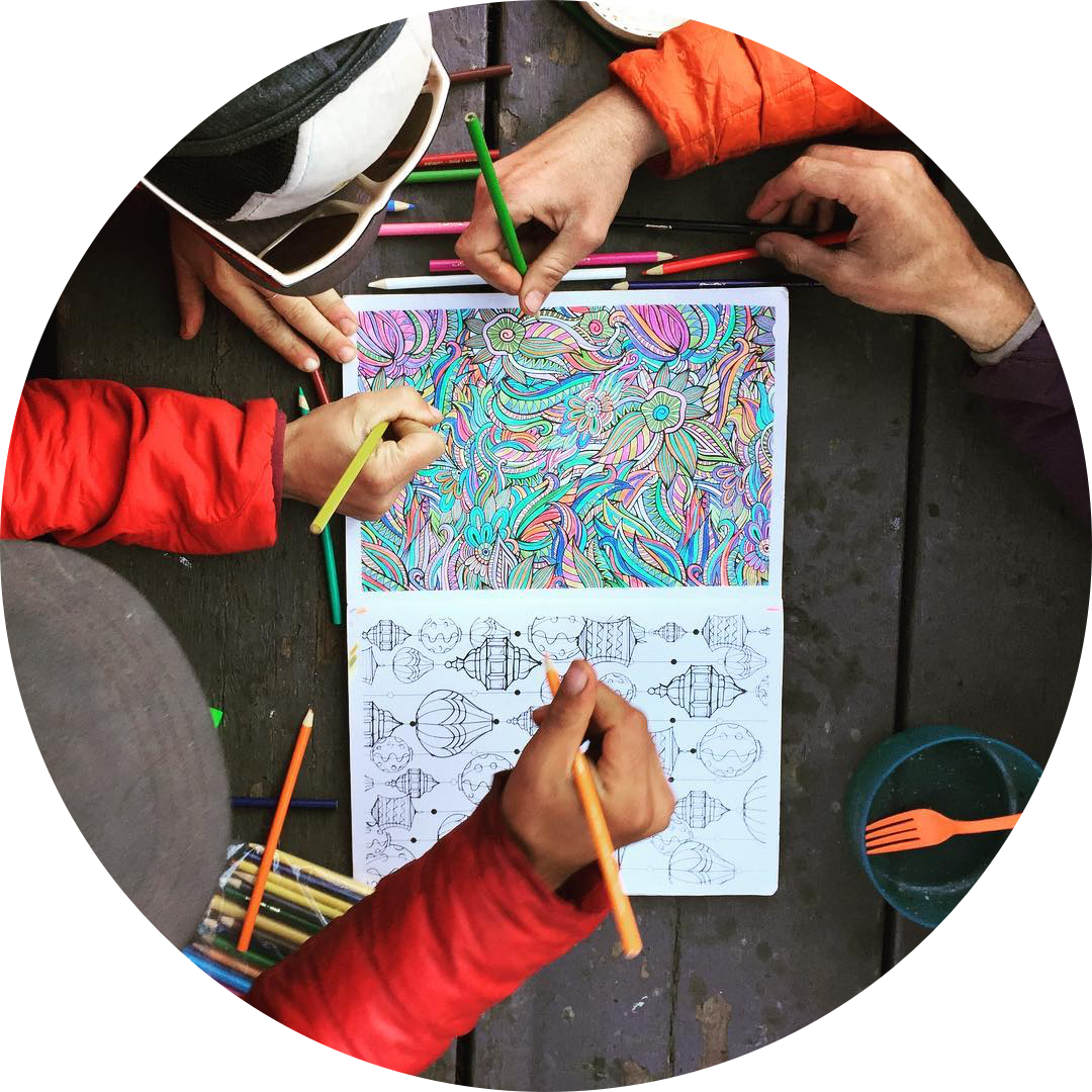 Overhead shot of five hands collaborating on an intricate coloring page with colored pencils.