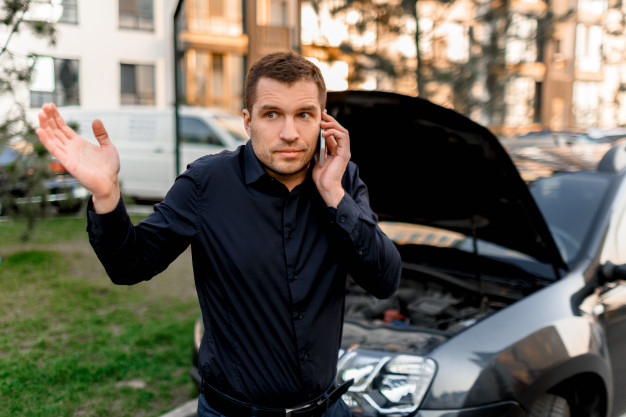 Car breakdown concept. the car will not start. a young man is calling for a car service. they cannot fix the car on their own. insurance must cover all costs. Premium Photo