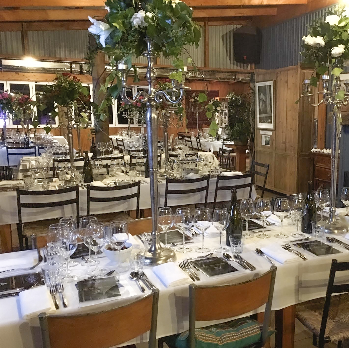 Tables fully prepared with cutlery, glassware and greenery