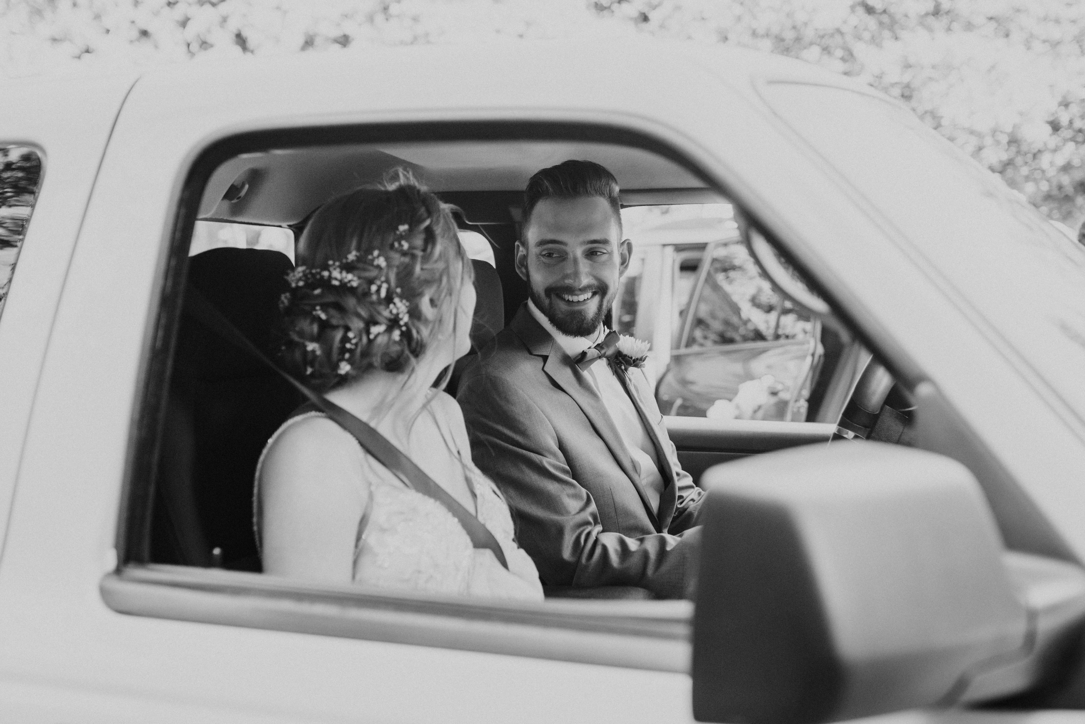 Bride and groom in car driving towards their honeymoon, wedding photography inspiration