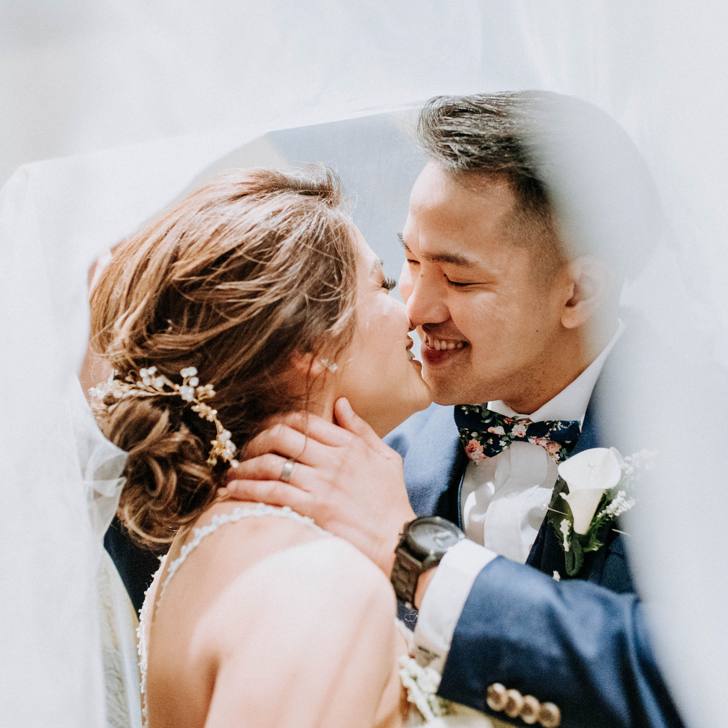 just married couple goes in for kiss under veil after tying the knot, sweet wedding photo inspiration
