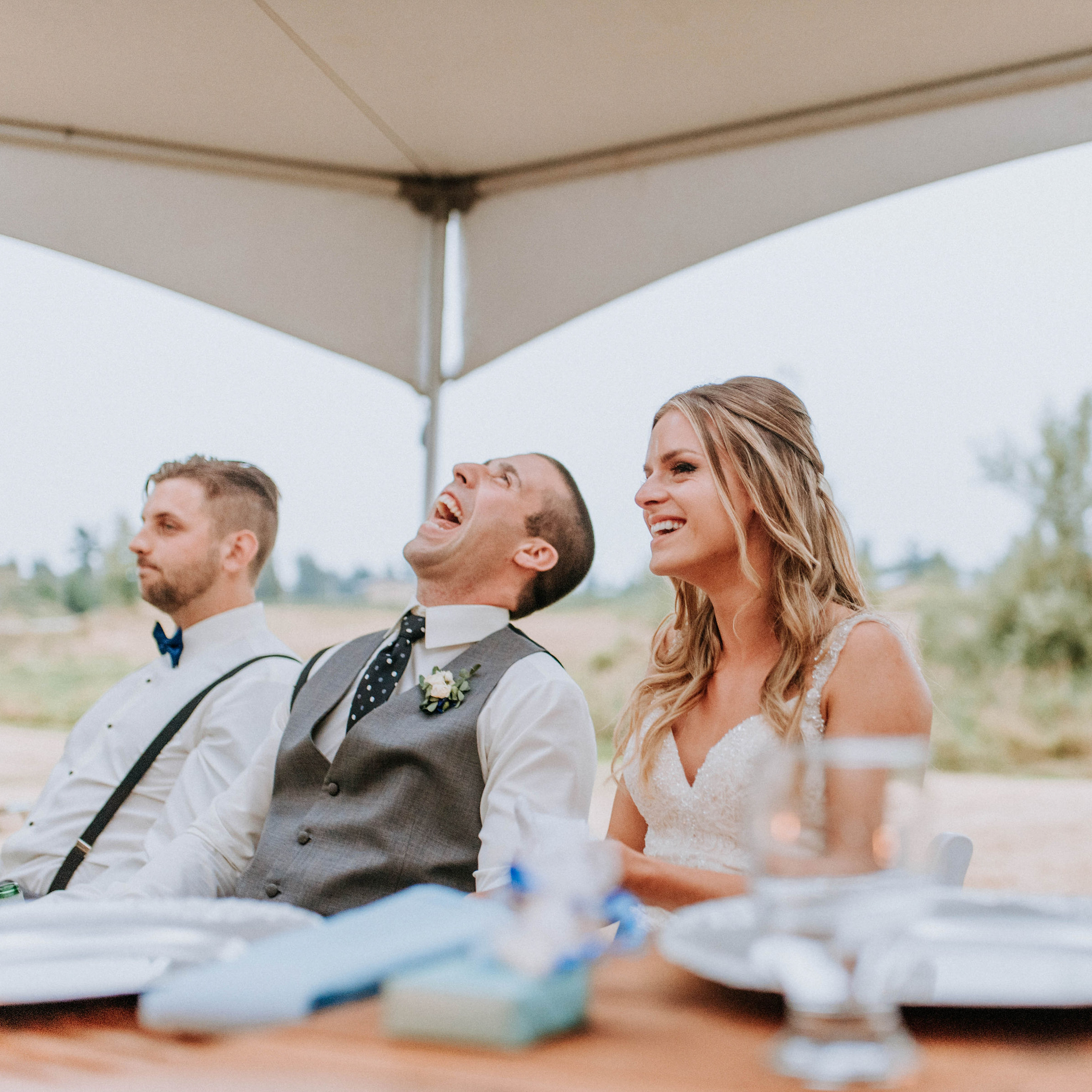 wedding couple laughing during wedding speeches at sunset outdoor reception under white tents on the family farm in Chilliwack, BC