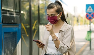 Woman coughing while looking at her phone and wearing a mask. Hyfe - Start tracking your cough now with our cough monitoring App