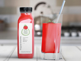 Smoothie bottle with white label next to glass with straw in it