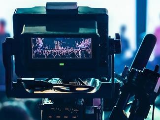 A video camera recording an outdoor festival