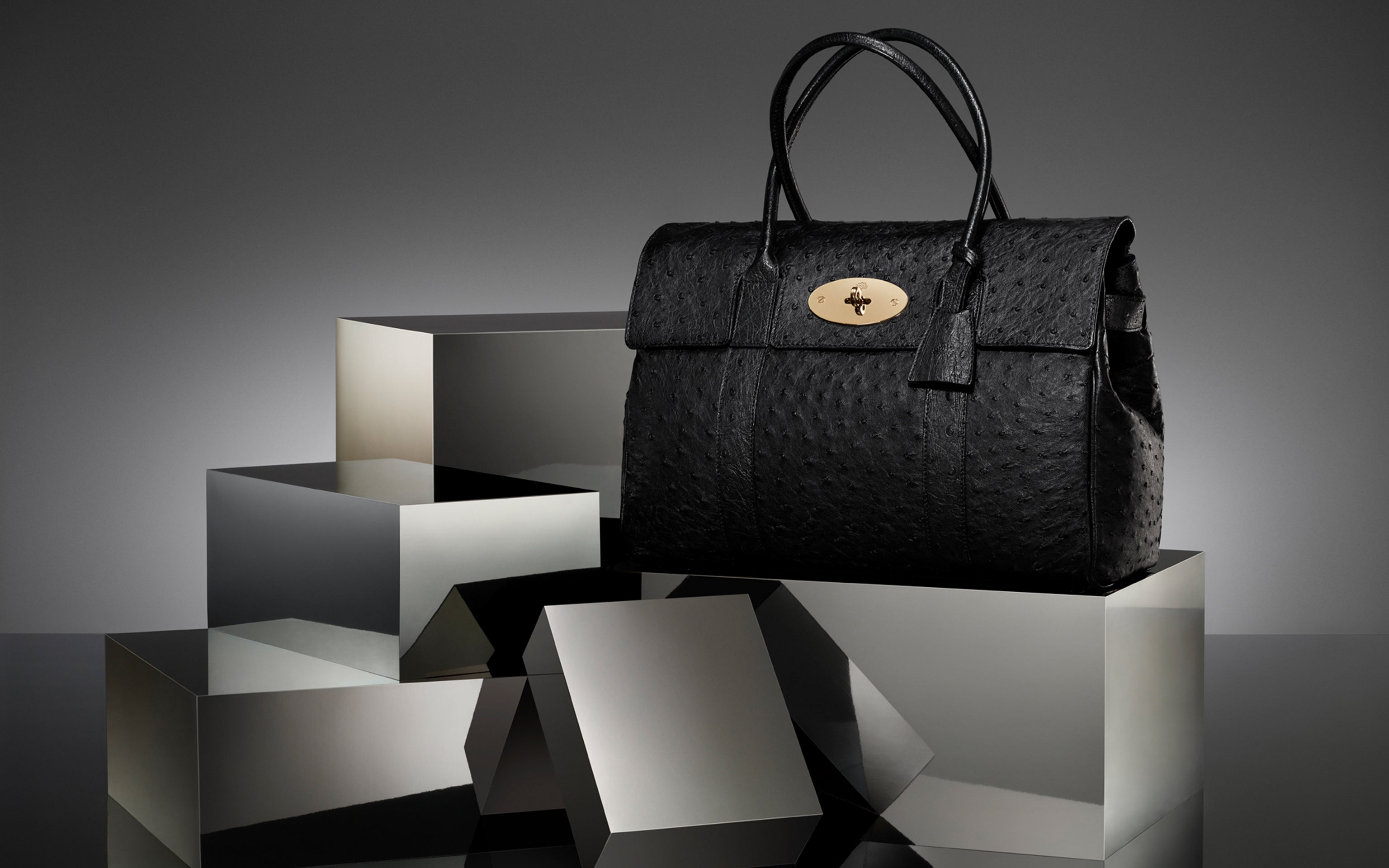 black handbag with gold buckle on grey silver reflecting scene