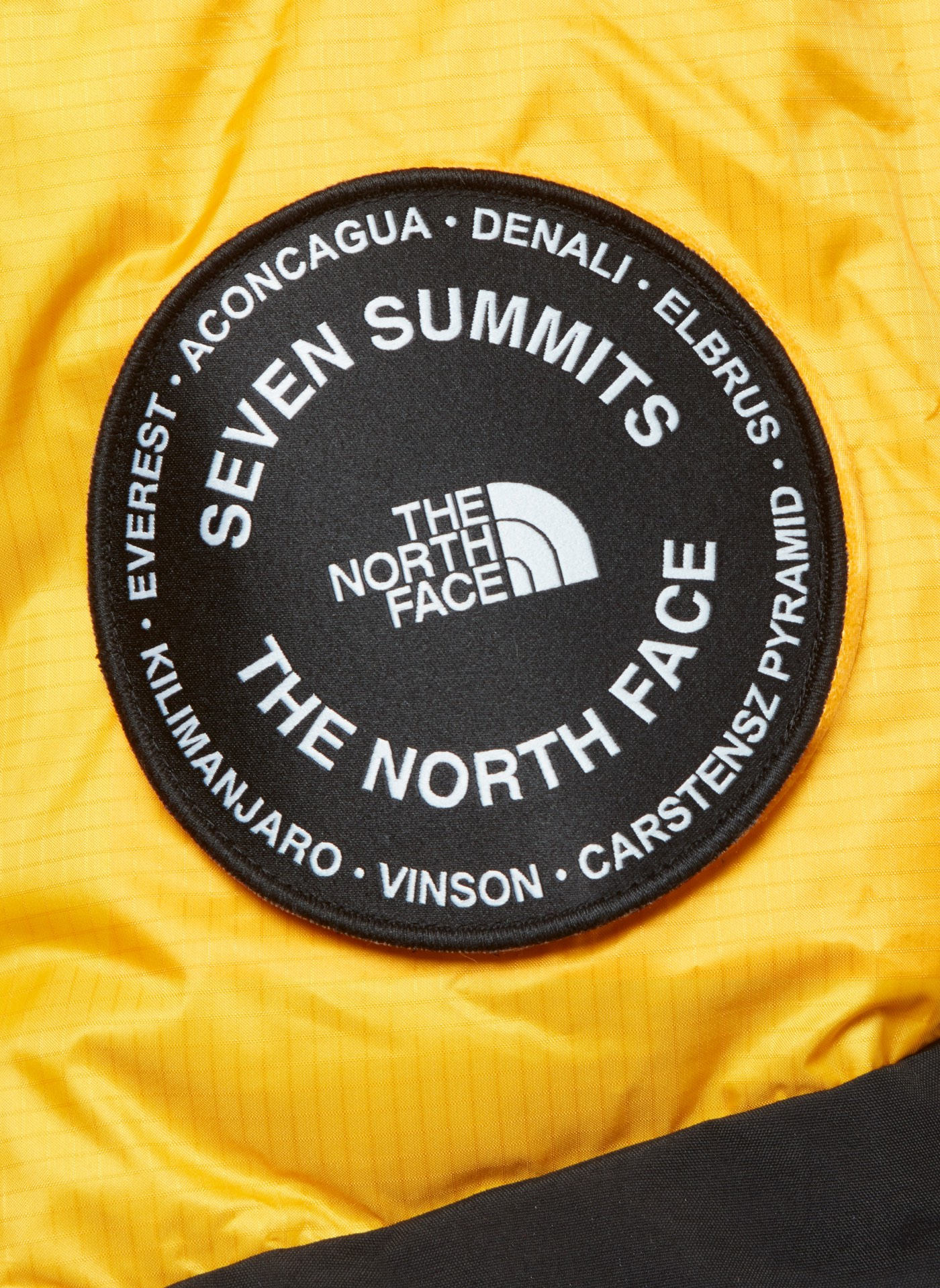 the north face logo on a yellow jacket