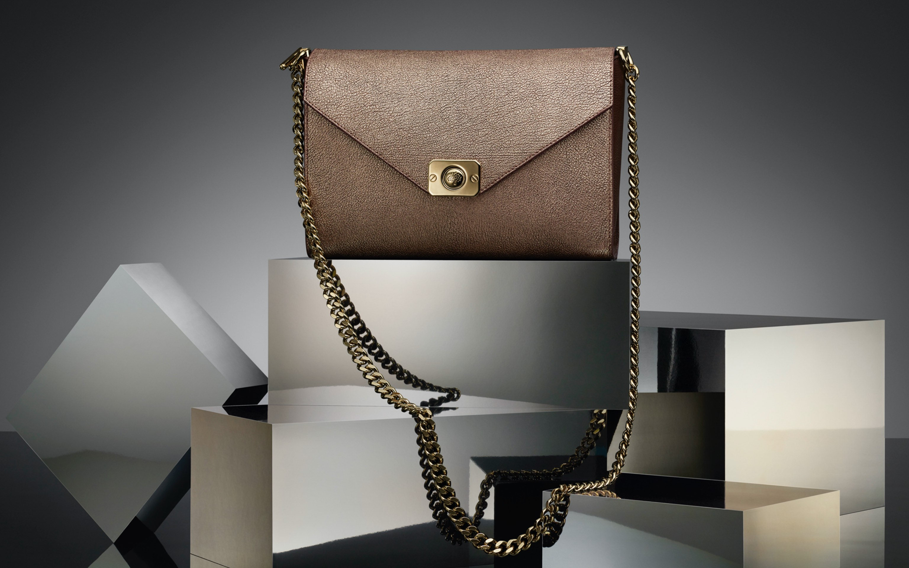 creative commercial shot of bronze colour bag in grey reflecting scene