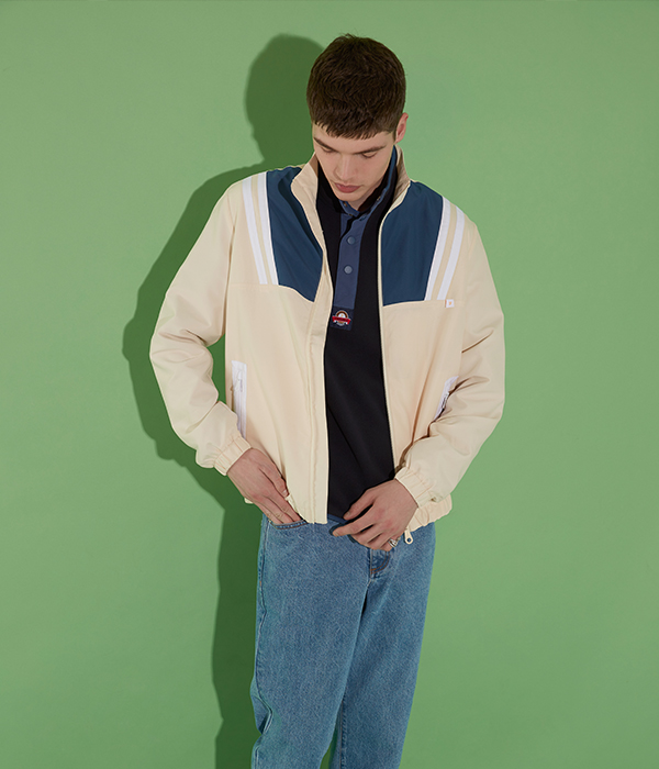 Menswear model wearing blue jeans and white jumper posing on green background