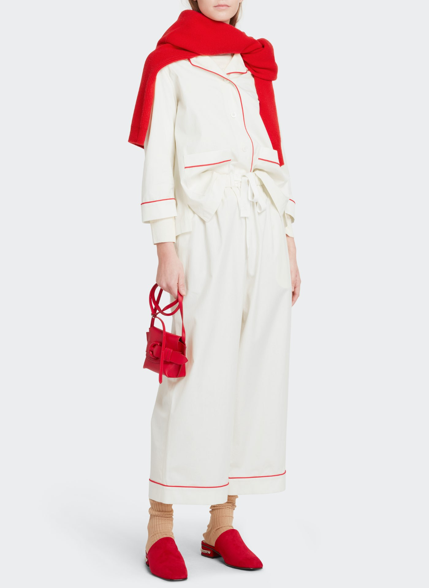 Womenswear model wearing white J&M suit with a red leather bag, red shoes and red scarf