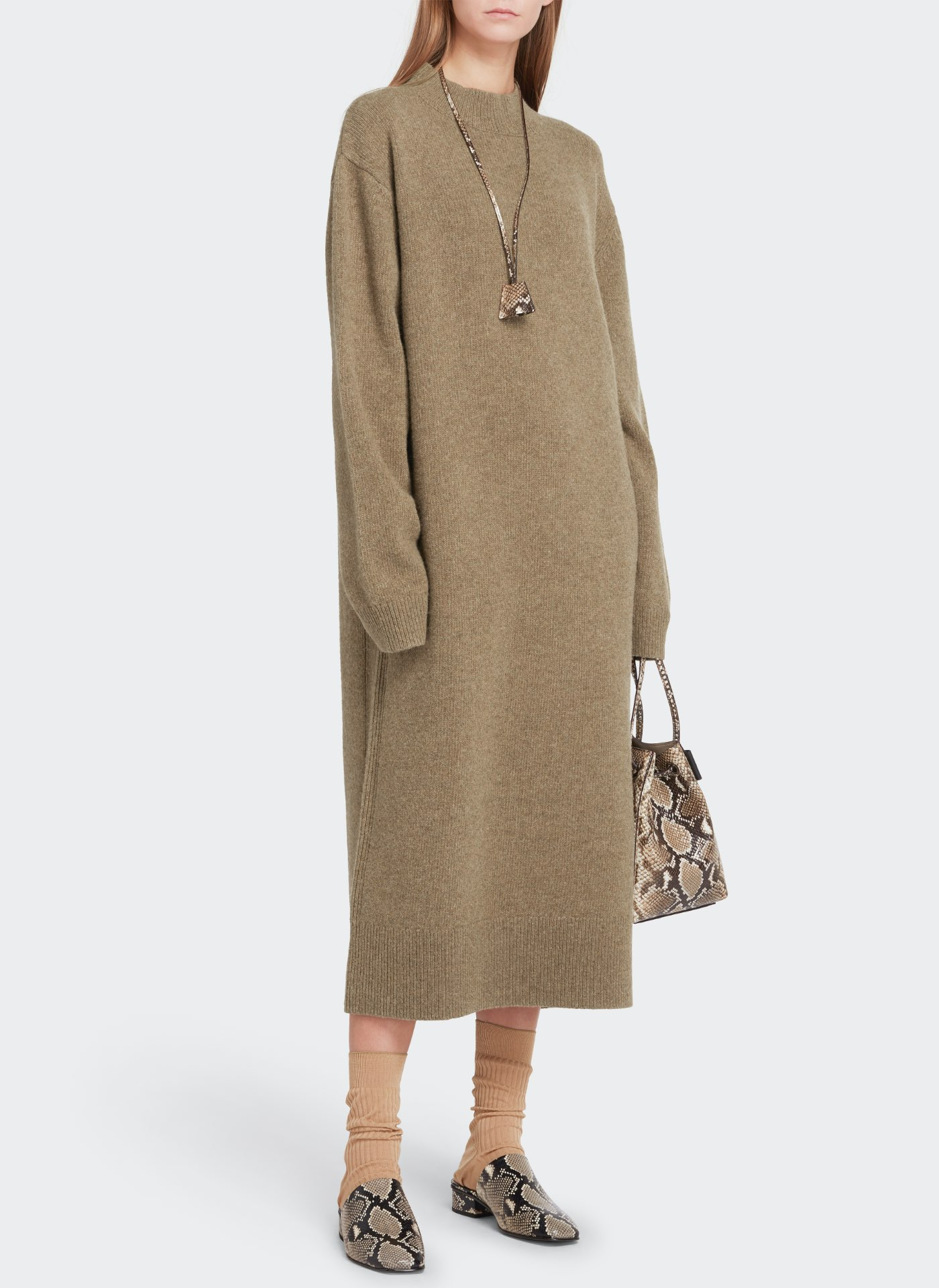 Womenswear model wearing pale moss long sweater dress with a camo pattern leather bag