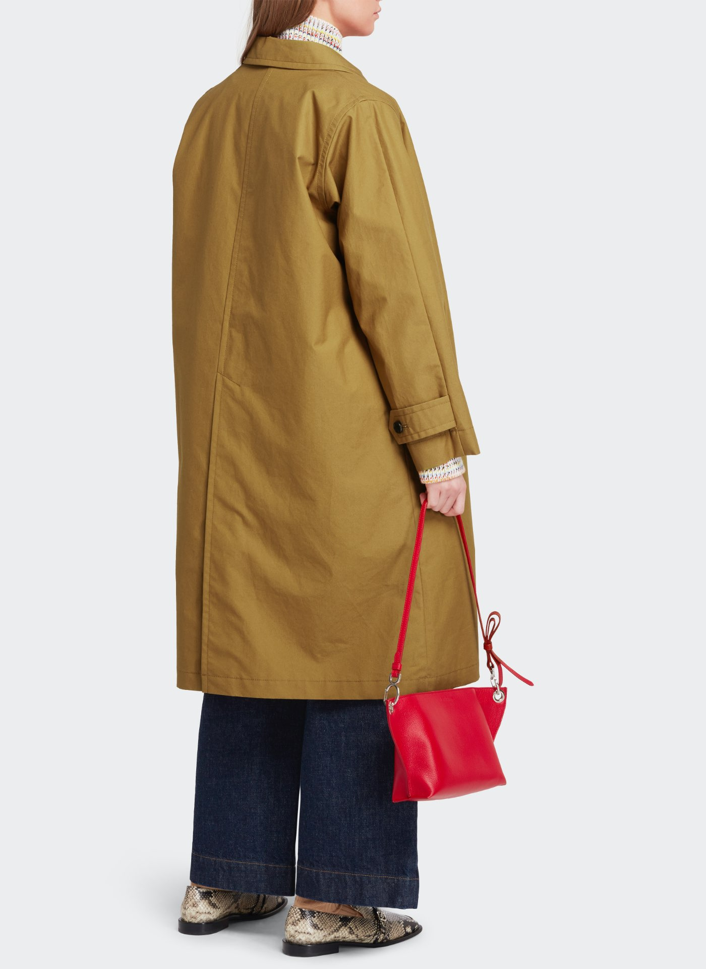womenswear model with a long light brown jacket, red leather bag and dark blue jeans