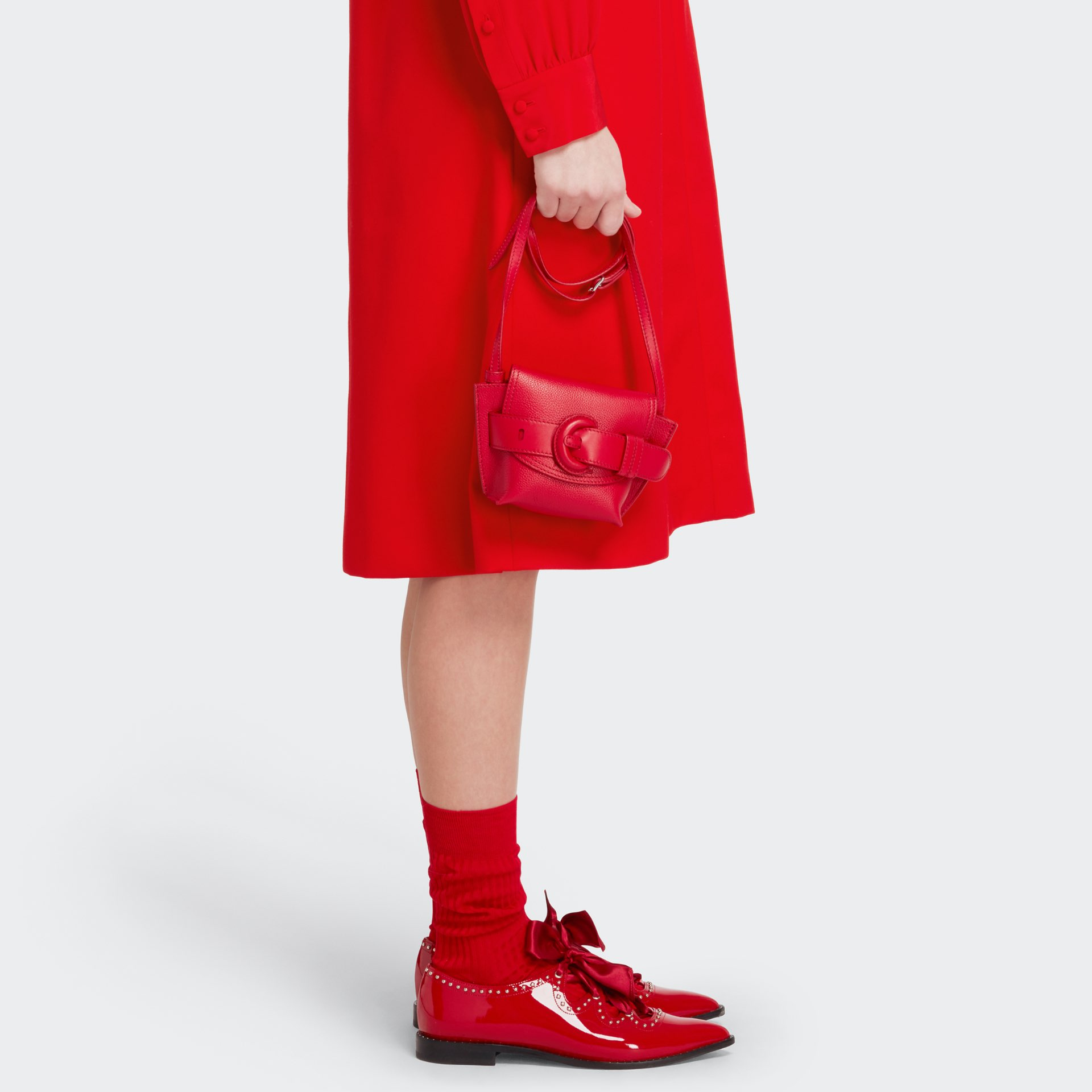 Womenswear model wearing red J&M dress with a red leather bag, red shoes and ed socks