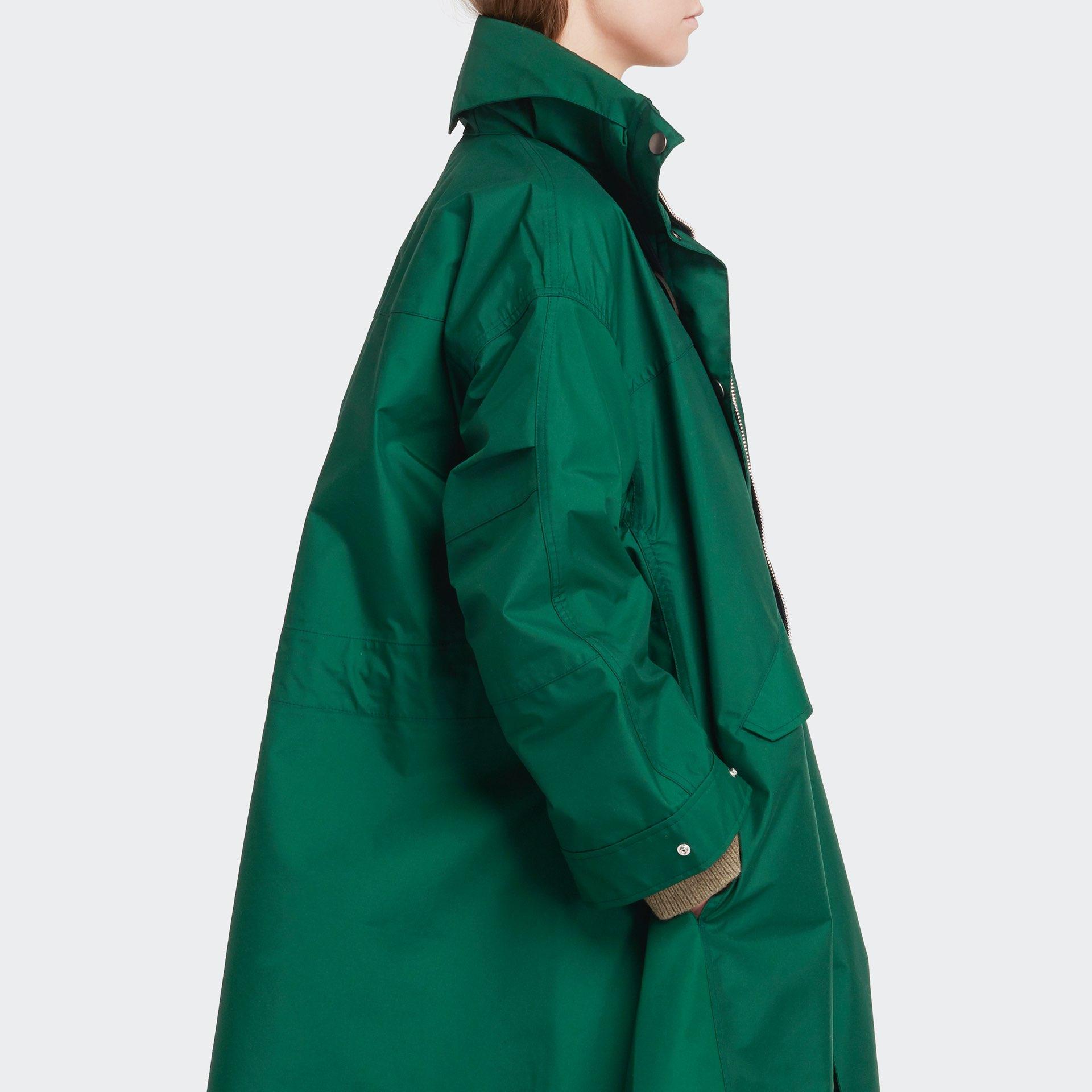 side shot of the womenswear model wearing long green raincoat