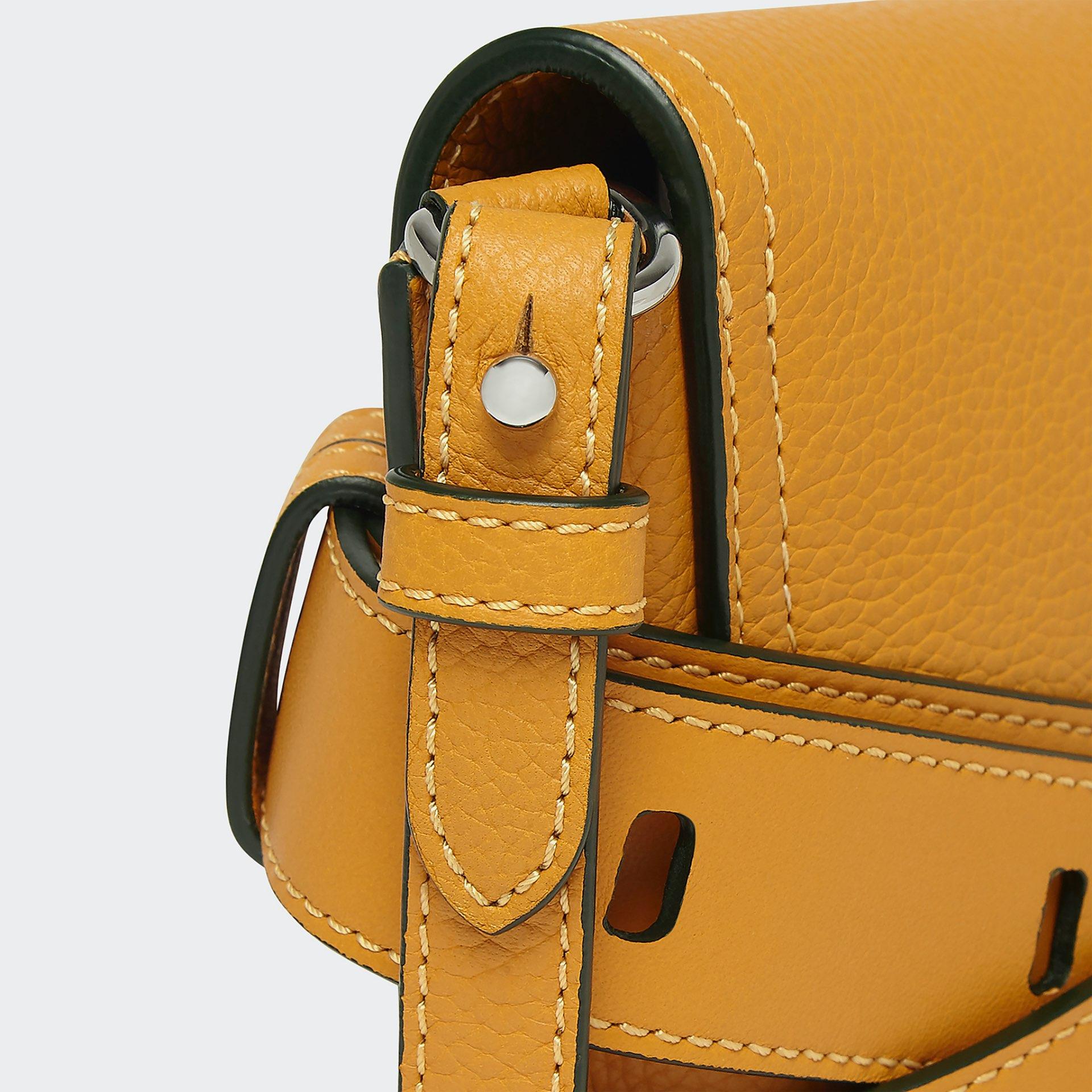 detail shot of J&M mustard yellow small handbag