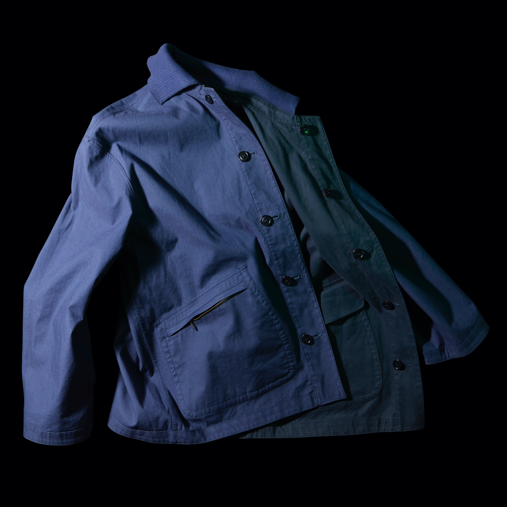 blue C.P. Jacket on black background laid creatively with contrast light