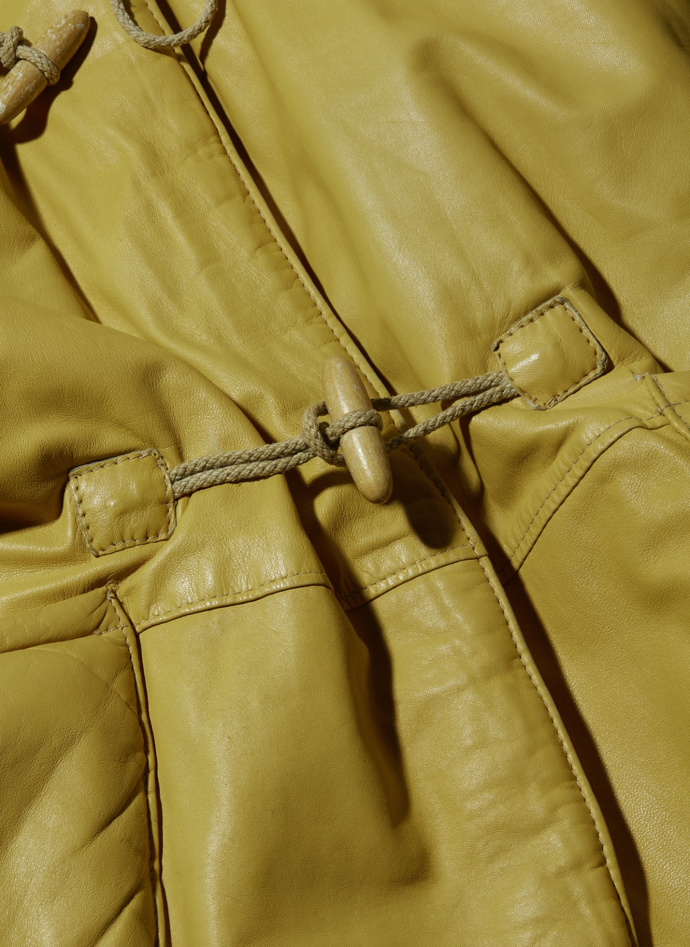 C.P. Company mustard yellow leather coat detail shot of button
