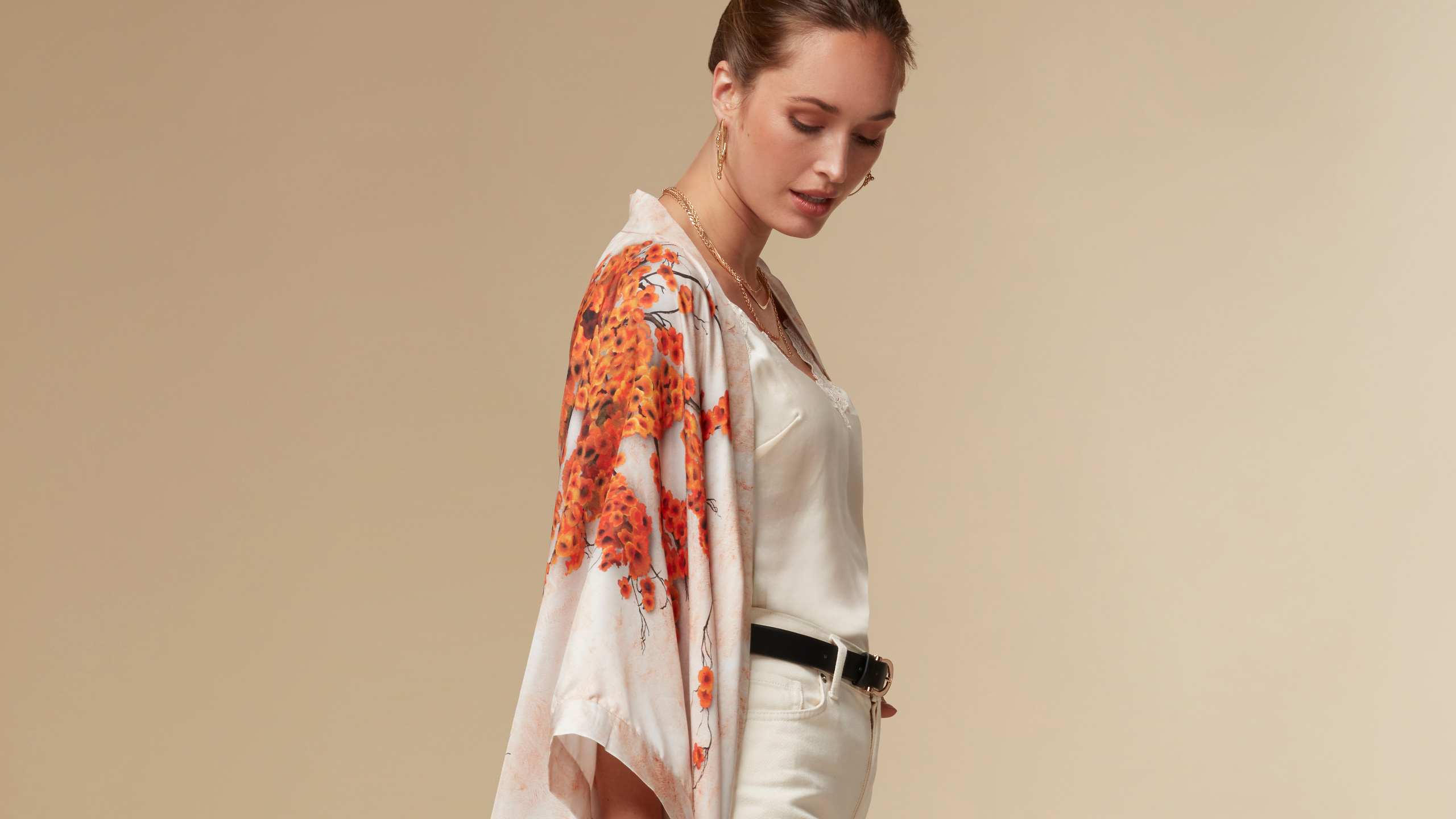 womenswear model wearing a kimono in a beige background