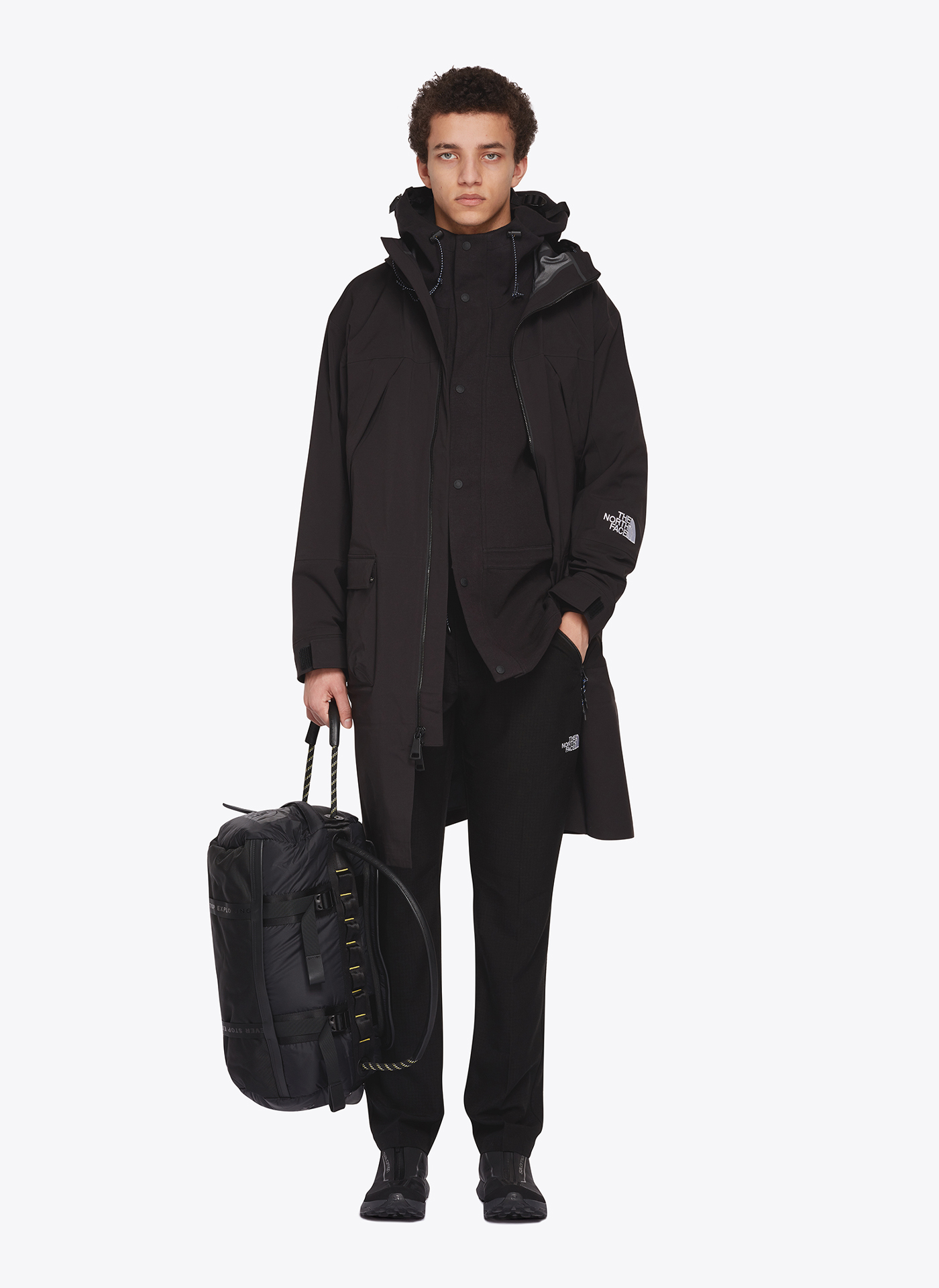 e-commerce menswear model wearing all black street style coat and trousers with handbag