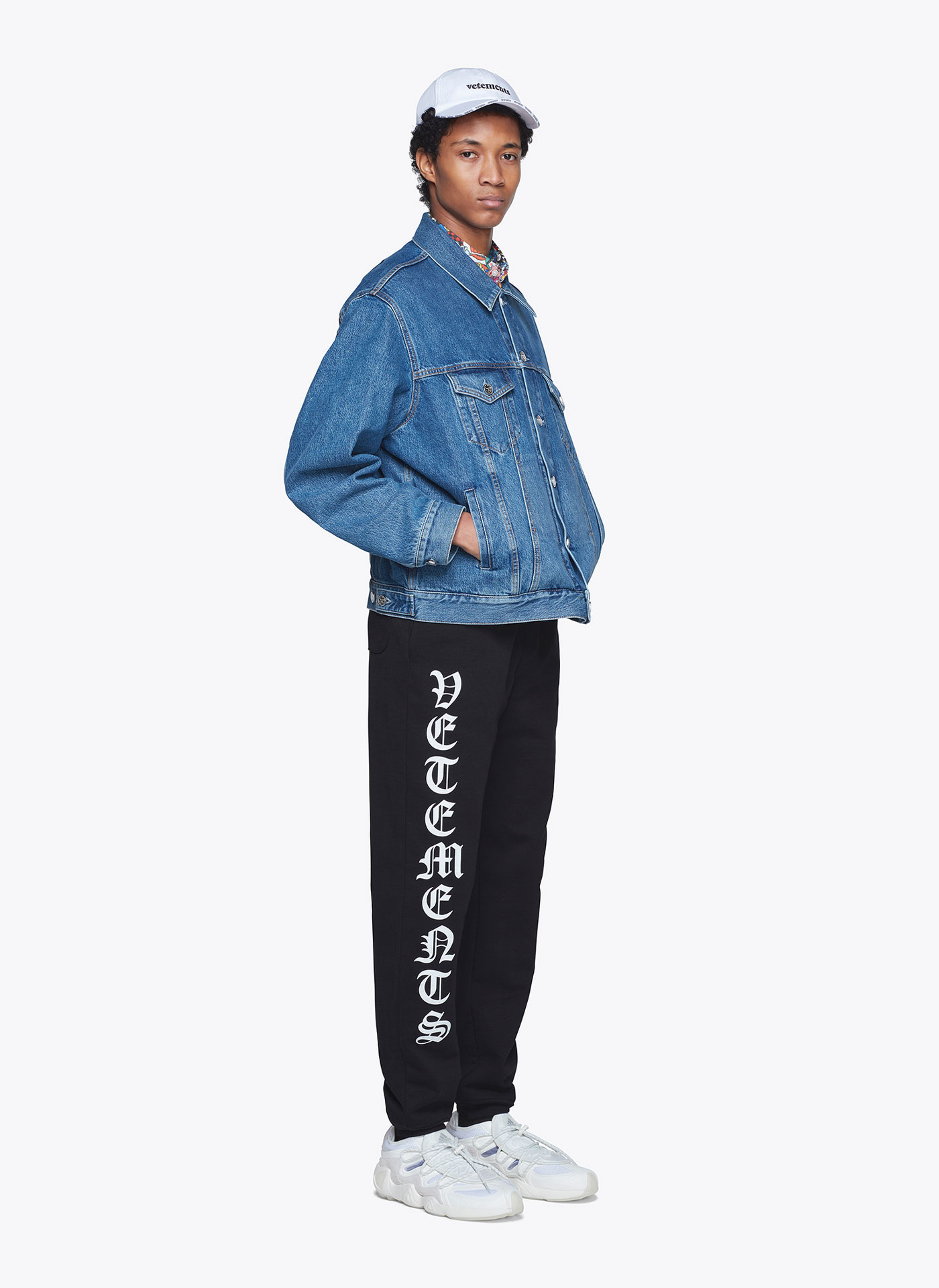 meanswear model with denim jacket, black jogger trousers and a white cap