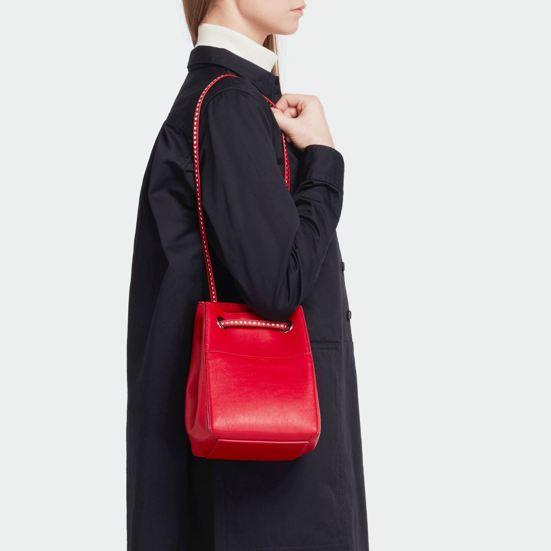womenswear model wearing red J&M leather bag with dark blue coat