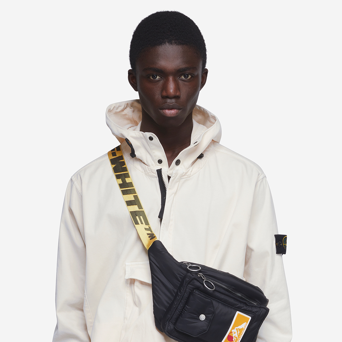 Menswear model wearing stone island white jacket and off white bag
