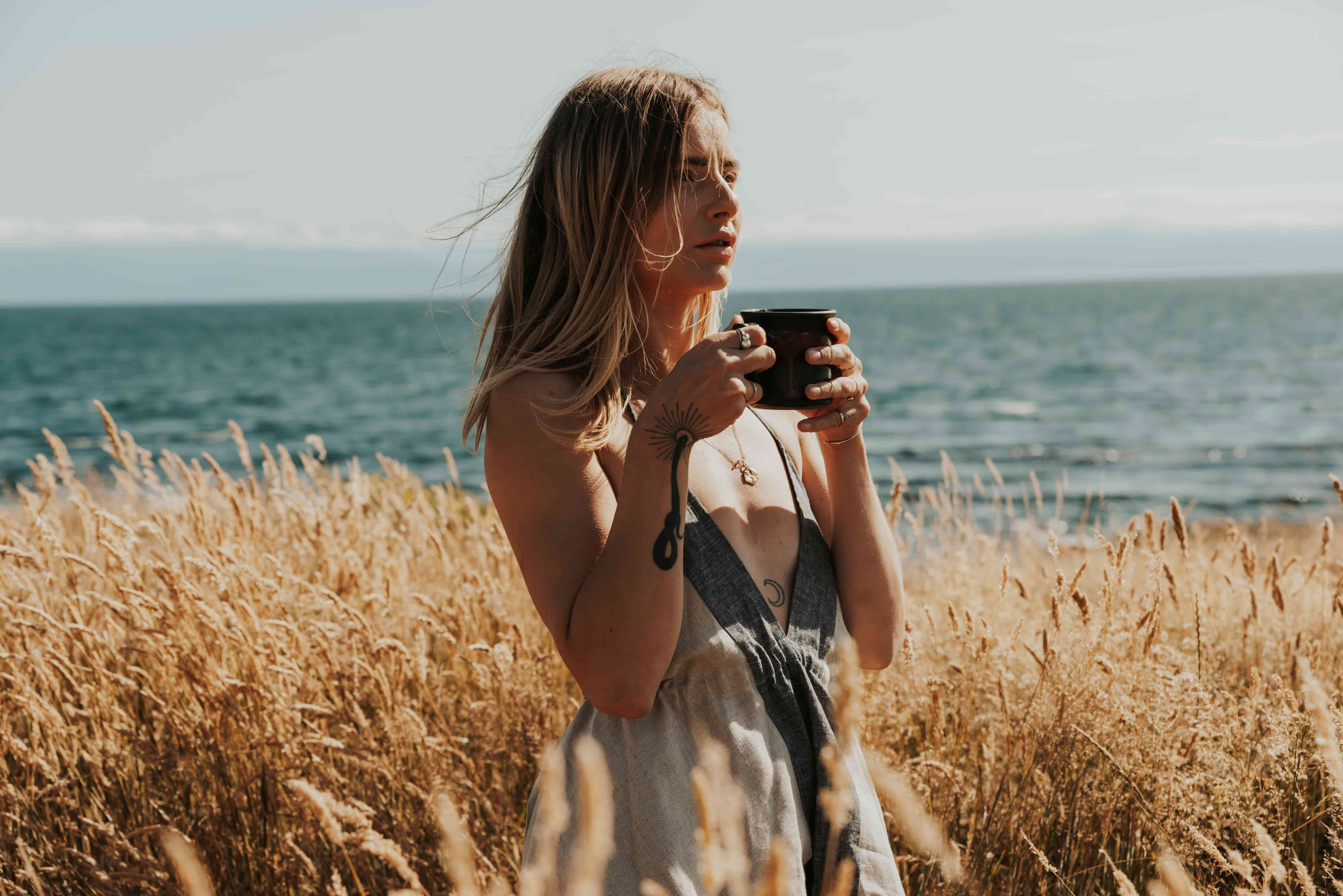 Haley Salomon with a cup of Herbal Honest Tea in a field of gold grass by the ocean in a photo by Hailey Krakana.