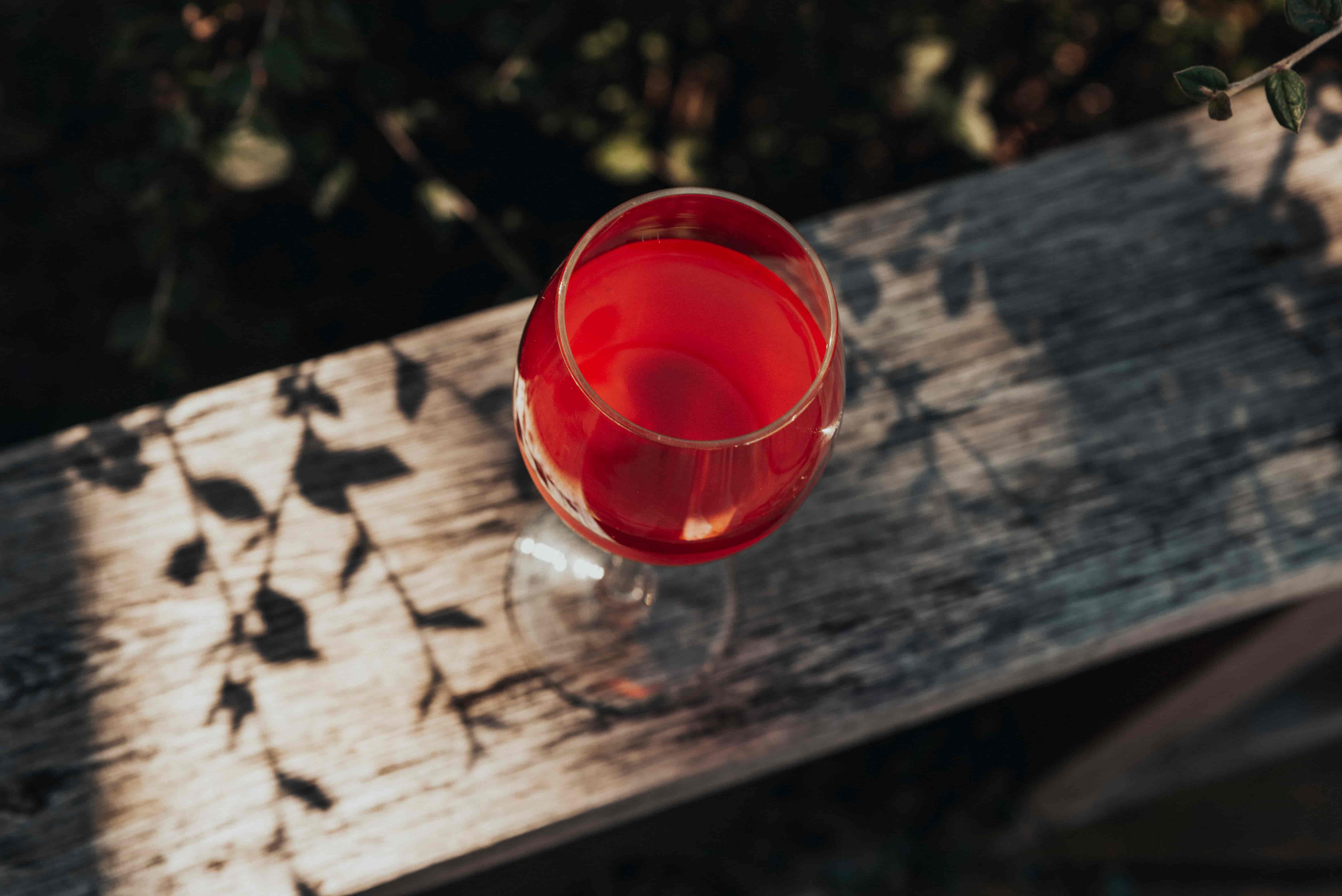 A wine glass of kombucha made with Herbal Honest Tea on a deck